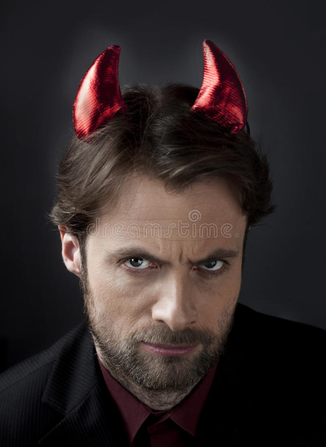 Man in suit with devil horns - concept of cruel boss stock photography
