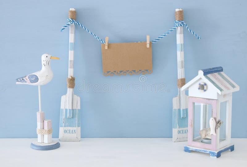 concept nautique avec accrocher la note vide sur une ficelle à côté de maison de plage et la mouette au-dessus du fond bleu photographie stock