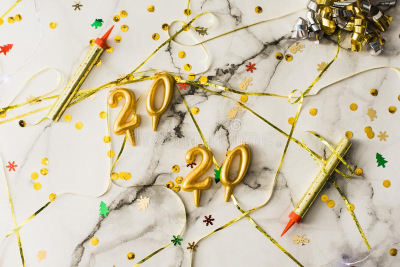 The concept of the new 2020 and Christmas. Candles in the shape of numbers 2020 as a symbol of the new year next to christmas. Shaped sparkler candles fountain royalty free stock photography