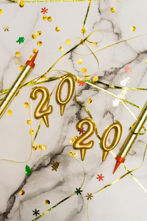 The concept of the new 2020 and Christmas. Candles in the shape of numbers 2020 as a symbol of the new year next to christmas. Shaped sparkler candles fountain royalty free stock photos