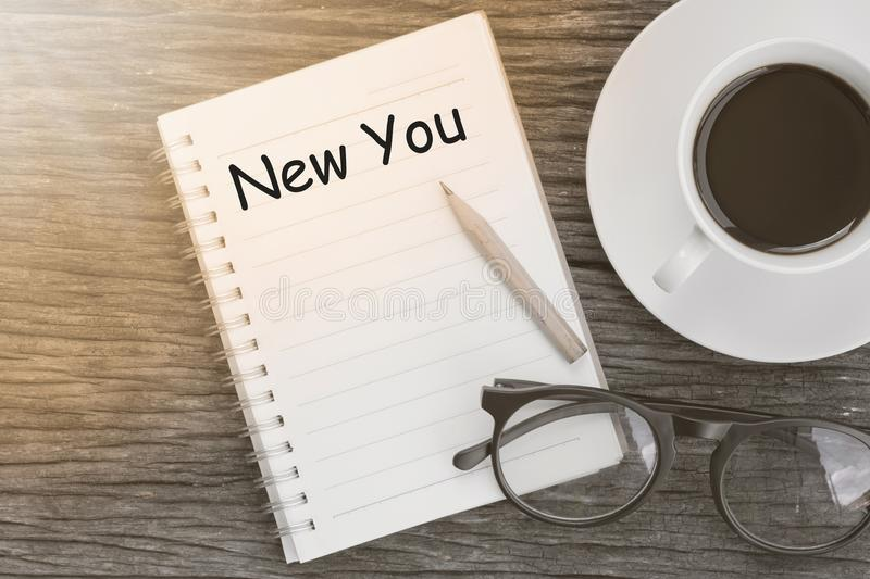 Concept new you message on notebook with glasses, pencil and coffee cup on wooden table. royalty free stock photo