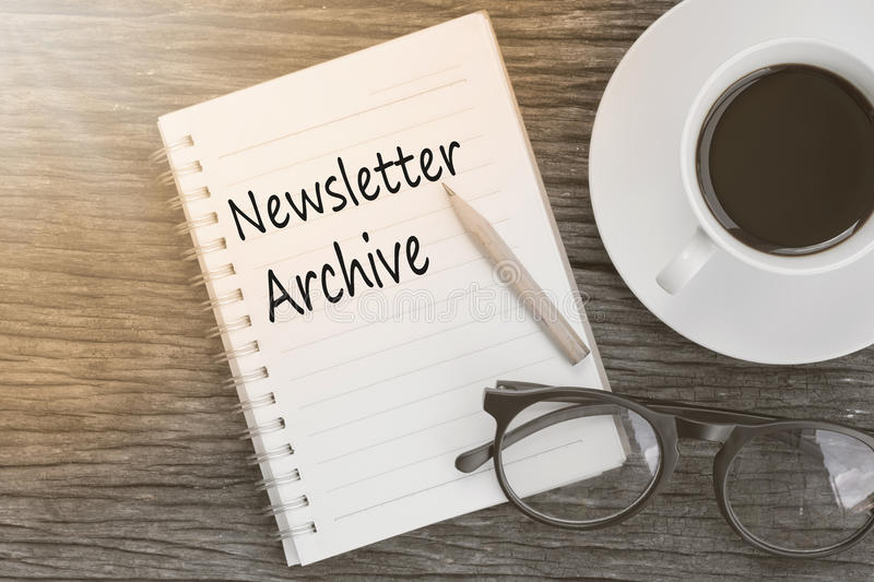 Concept Newsletter Archive message on notebook with glasses, pen. Cil and coffee cup on wooden table royalty free stock images