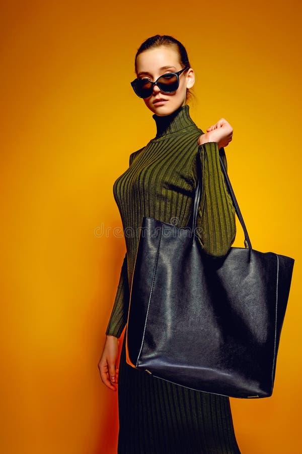 Concept noir de vente de vendredi Femme d'achats jugeant le sac en cuir noir d'isolement sur le fond jaune photos libres de droits