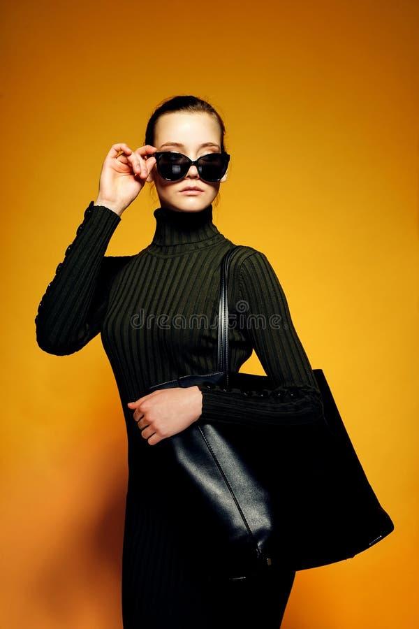 Concept noir de vente de vendredi Femme d'achats jugeant le sac en cuir noir d'isolement sur le fond jaune photo libre de droits