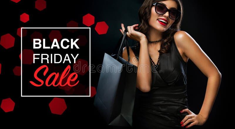 Concept noir de vente de vendredi Femme d'achats jugeant le sac gris d'isolement sur le fond foncé dans les vacances images libres de droits
