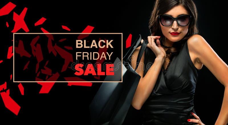 Concept noir de vente de vendredi Femme d'achats jugeant le sac gris d'isolement sur le fond foncé dans les vacances photographie stock