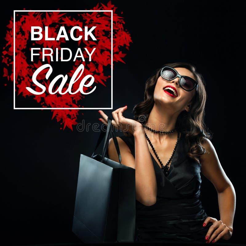 Concept noir de vente de vendredi Femme d'achats jugeant le sac gris d'isolement sur le fond foncé dans les vacances image stock