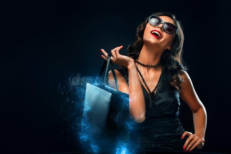 Concept noir de vente de vendredi Femme d'achats jugeant le sac gris d'isolement sur le fond fonc? dans les vacances images stock