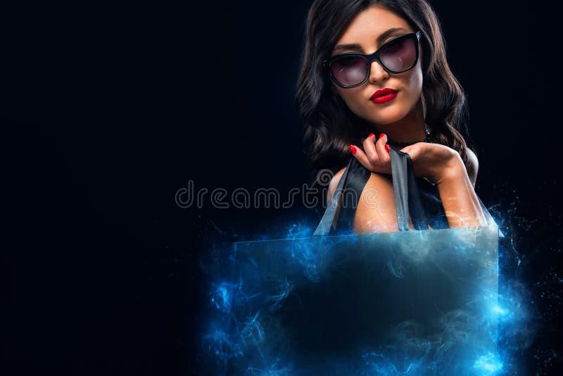 Concept noir de vente de vendredi Femme d'achats jugeant le sac gris d'isolement sur le fond fonc? dans les vacances photographie stock
