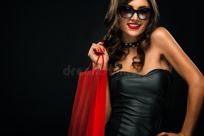Concept noir de vente de vendredi Femme d'achats jugeant le sac rouge d'isolement sur le fond foncé dans les vacances photo libre de droits