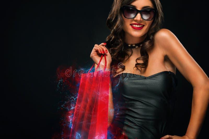 Concept noir de vente de vendredi Femme d'achats jugeant le sac rouge d'isolement sur le fond fonc? dans les vacances image stock