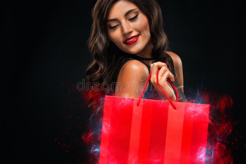 Concept noir de vente de vendredi Femme d'achats jugeant le sac rouge d'isolement sur le fond fonc? dans les vacances photo libre de droits