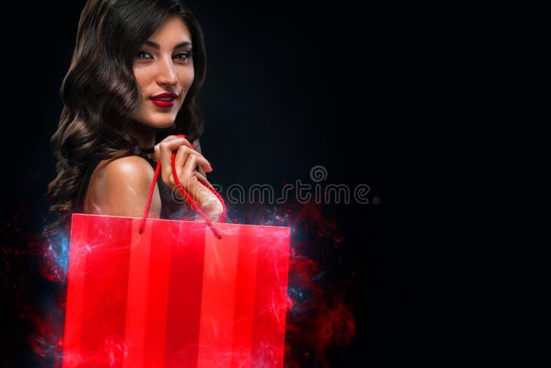 Concept noir de vente de vendredi Femme d'achats jugeant le sac rouge d'isolement sur le fond fonc? dans les vacances photos libres de droits
