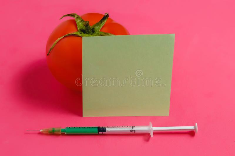 Concept of Non-natural Products, Gmo. Syringe, Sticker and Red Tomato on Pink Background, stock photos