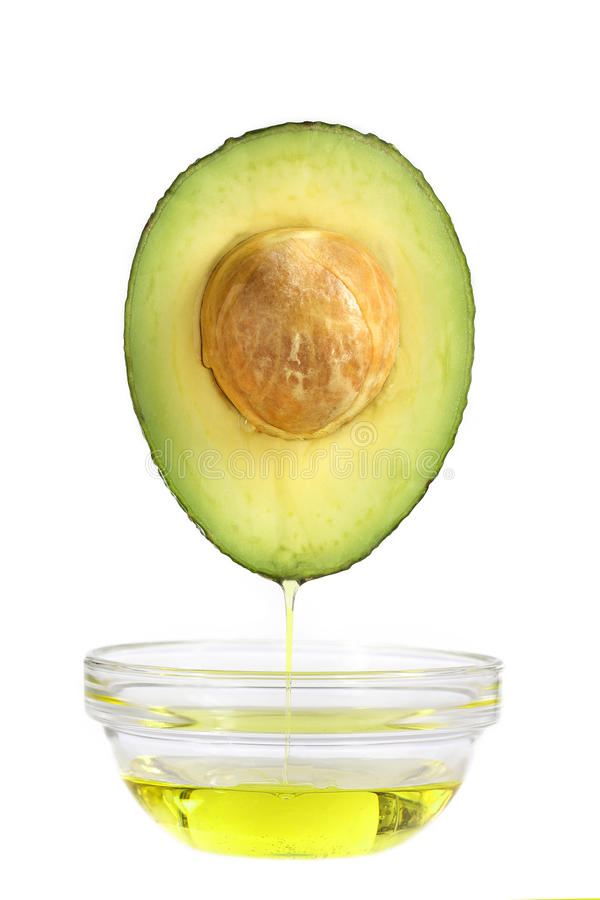 Concept of oil from avocado falling in a cup on royalty free stock photos