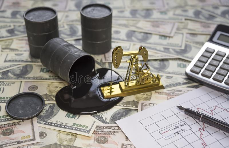 The concept of the oil business. Barrels of oil are worth a dollar money banknote, a gold drilling pump, a calculator. A growth chart of products and imports stock photography