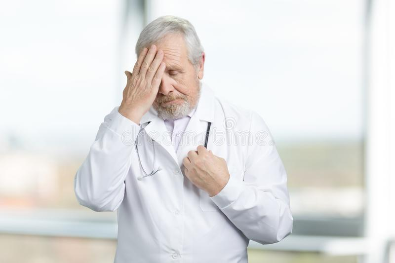 Concept of old doctor regret about mistake, feeling sorry. Doctor thoughtfully put his hand to his head and ponders stock images