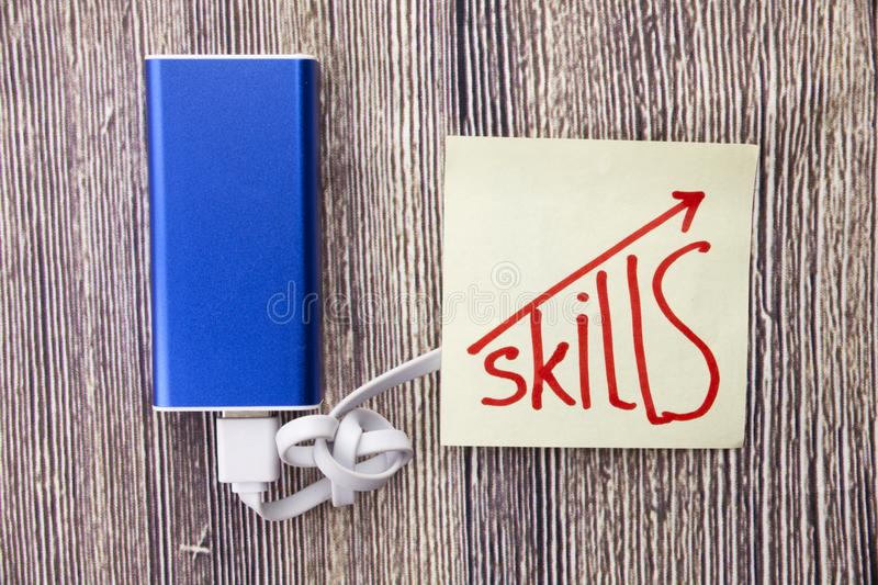 Concept of online learning methods. Charging bank with concept of upgrading online skills. Handwritten word skills on the white pa stock photos