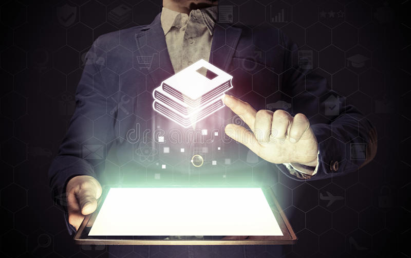 Concept of online library. Education. Man touches to stack of books icon. He holds tablet pc, that contains a many different online services stock photography