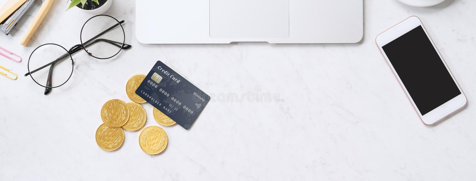 Concept of online payment with credit card with smart phone, laptop computer on office desk on clean bright marble table royalty free stock photo