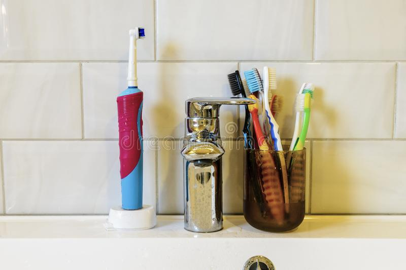 concept of oral hygiene of a large family. many different toothbrushes on the background of the faucet and the sink stock images