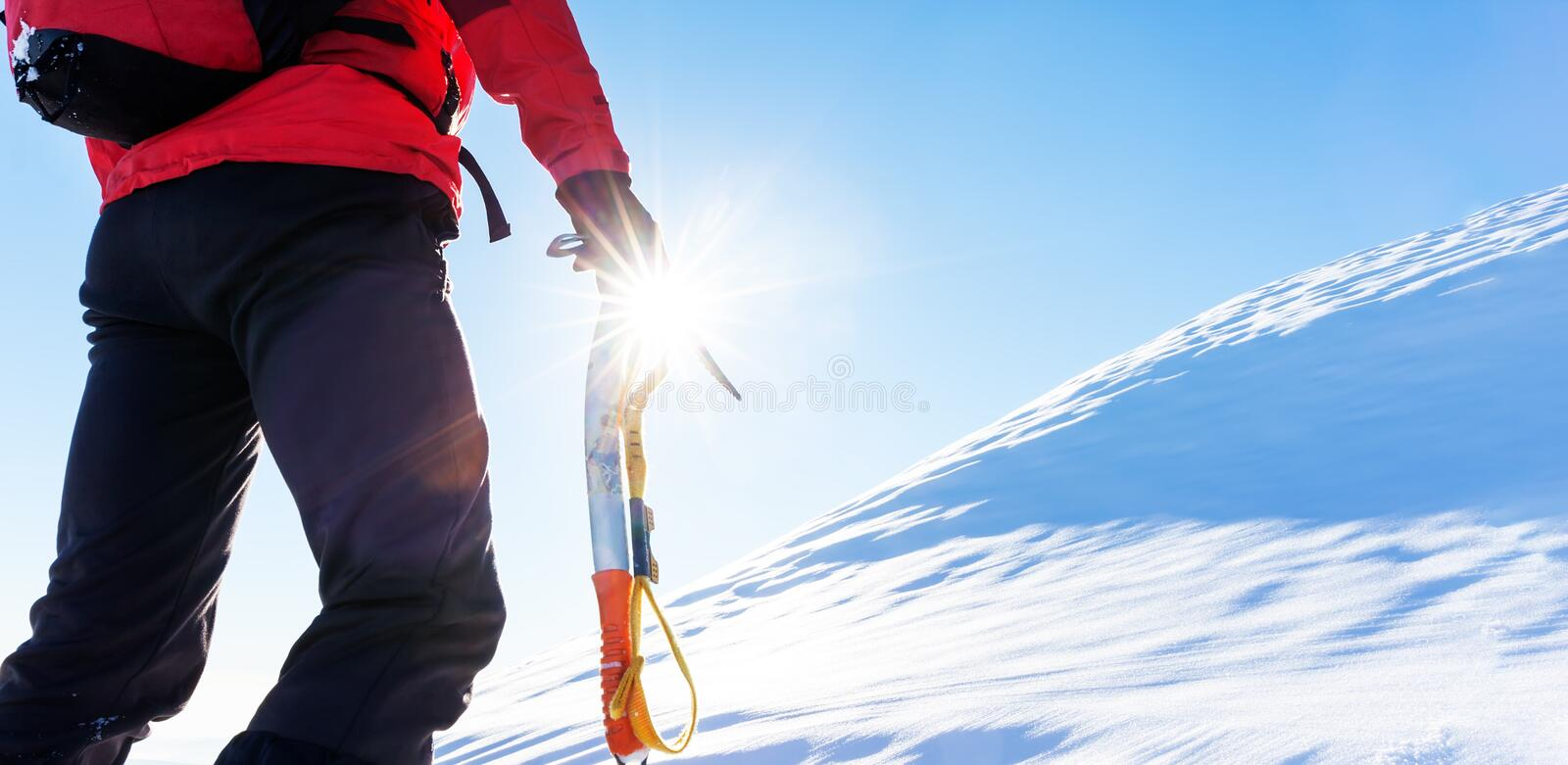 Concept: overcome challenges. Mountaineer faces a climb at the t. Op of a snowy peak stock image
