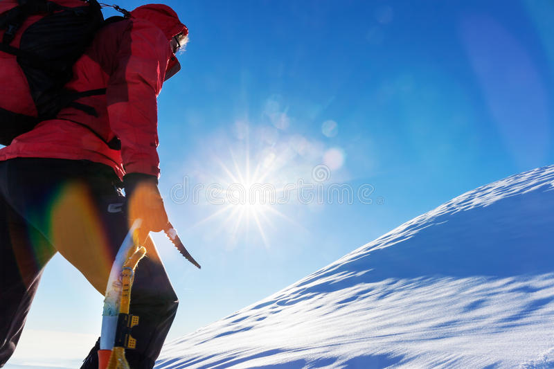 Concept: overcome challenges. Mountaineer faces a climb at the t. Op of a snowy peak royalty free stock images