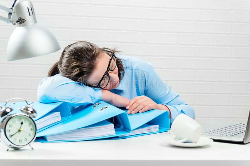 Concept - overtime in the office, tired accountant in the report royalty free stock photo