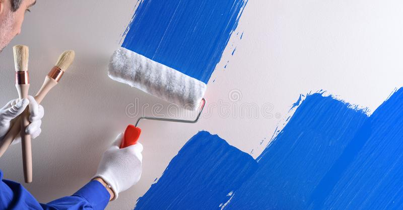 Concept of painter painting wall with blue paint royalty free stock photos