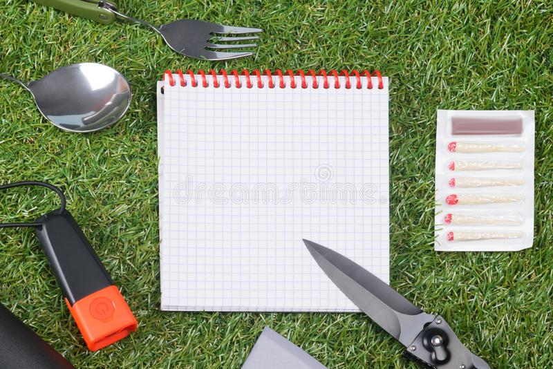 Concept, paper sheet and items for an expedition on green grass, close-up stock image