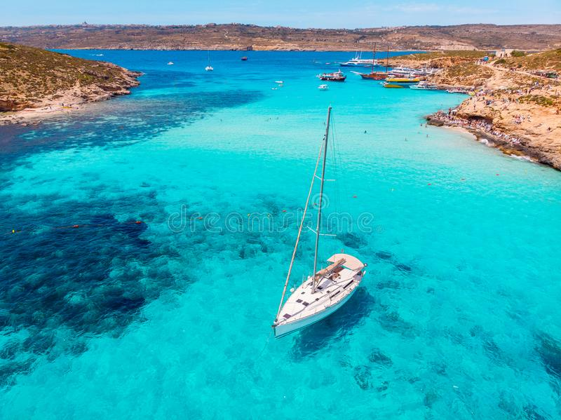 Concept paradise vacation. White yacht with sail in clear water of sea with sand. Blue Lagoon Comino Malta. Aerial view.  royalty free stock photo