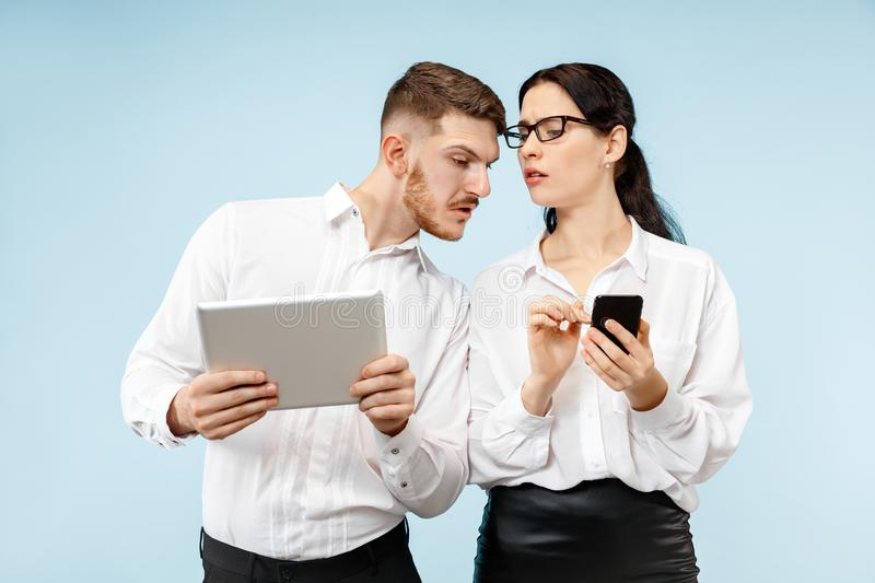 Concept of partnership in business. Young emotional man and woman standing at studio royalty free stock photos