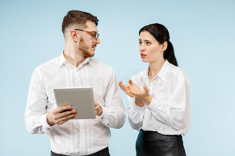 Concept of partnership in business. Young emotional man and woman standing at studio royalty free stock photography