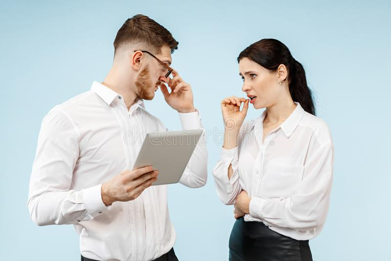 Concept of partnership in business. Young emotional man and woman standing at studio royalty free stock image