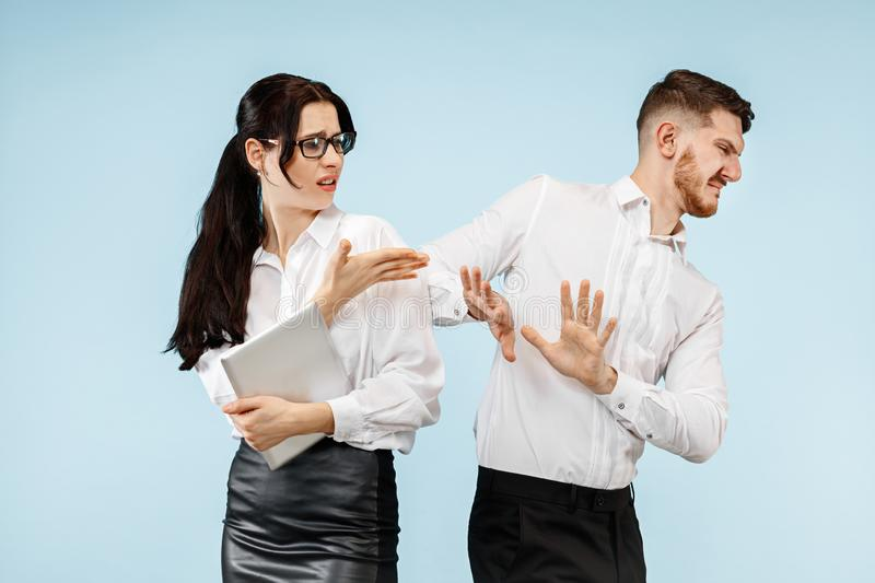 Concept of partnership in business. Young emotional man and woman standing at studio stock photo
