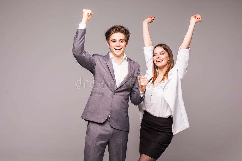 Concept of partnership in business. Young man and woman standing with raised hands against gray background. Winning emotions. royalty free stock photos