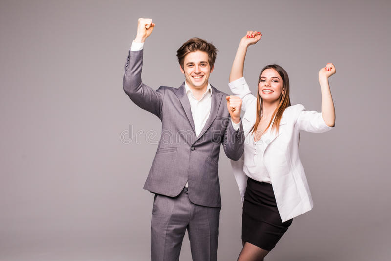 Concept of partnership in business. Young man and woman standing with raised hands against gray background. Winning emotions. stock photo