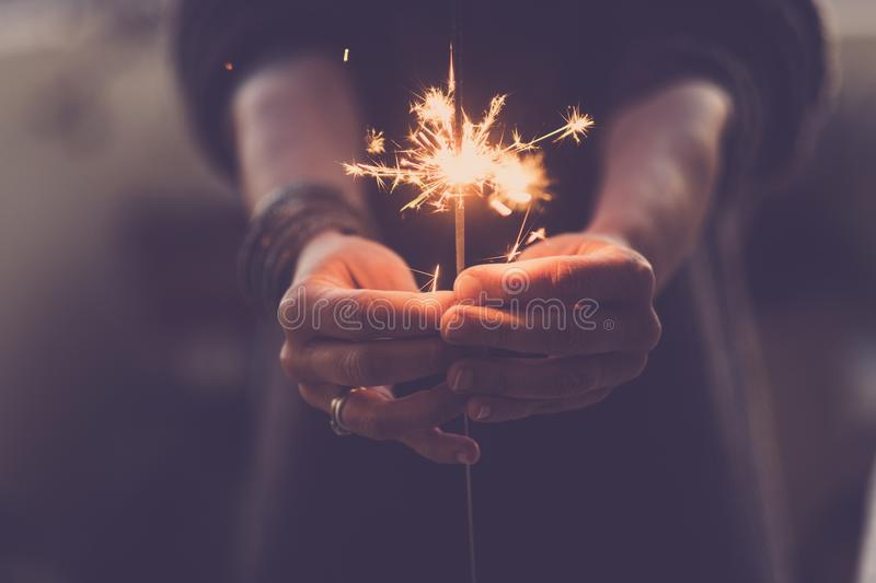 Concept of party nightlife and new year eve 2020 - close up of people hands with red fire sparklers to celebrate the night and the stock photos
