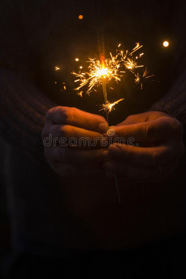 Concept of party nightlife and new year eve 2020 - close up of people hands with red fire sparklers to celebrate the night and the royalty free stock photography
