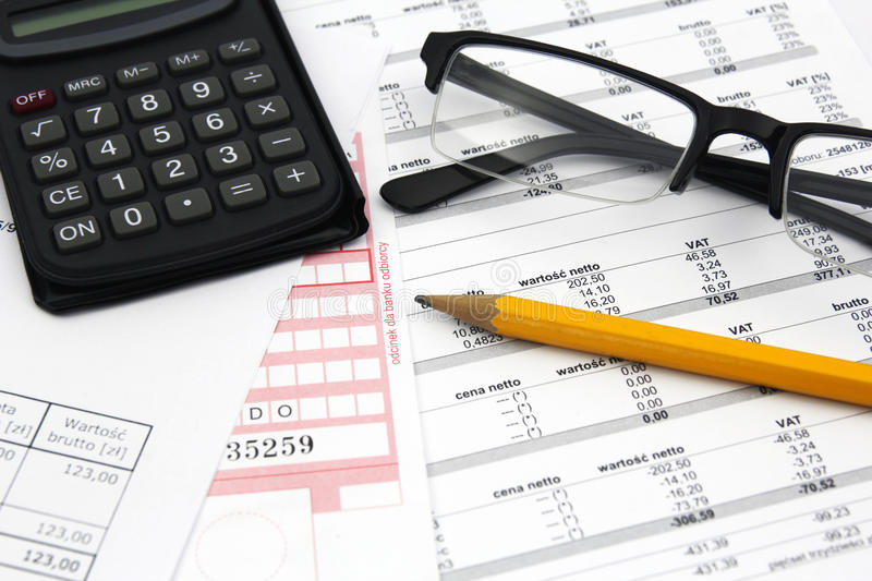 Concept of paying bills. Glasses, calculator and pencil on paper stock photography
