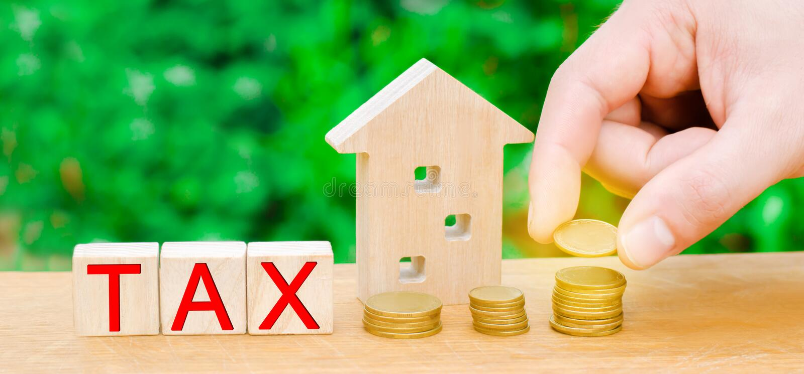 The concept of paying taxes on property and real estate. Saving money. House tax and risks. Hand puts a coin in a pile. Mortgage t. Ax royalty free stock photos