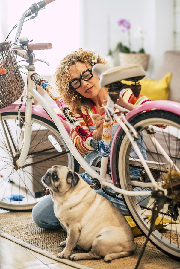 Concept of people friends with animal dog - woman work on a coloured funny bike at home with her best friend old pug is sit down. Near her - friendship and stock photography