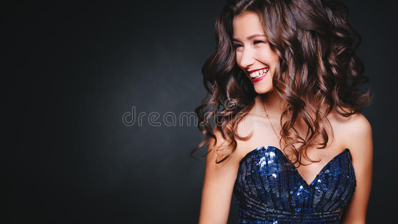 Concept perfect smile, fun. Young beautiful curly women in glitter dress on dark background. Copyspace. Celebration royalty free stock photography