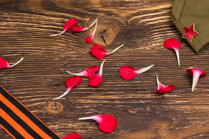 Concept from the petals of a red carnation, on an old wooden table royalty free stock photography