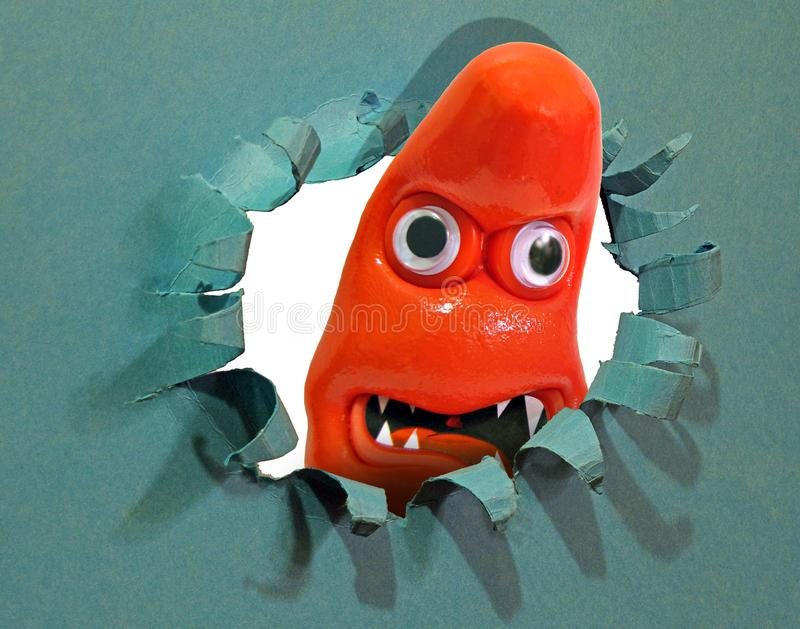 Blob monster looking through hole punched breakthrough burst tear royalty free stock photography