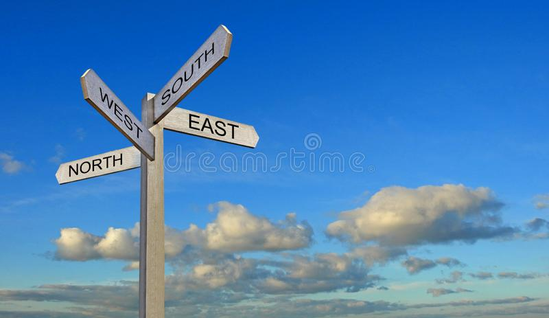 Blue sky clouds sign post arrows direction north south east west stock photos