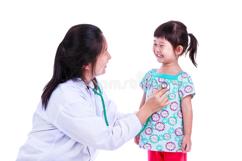 Concept photo of children health and medical care. Isolated on. Concept about children health and medical care. Caring medical doctor examining asian girl with royalty free stock photo