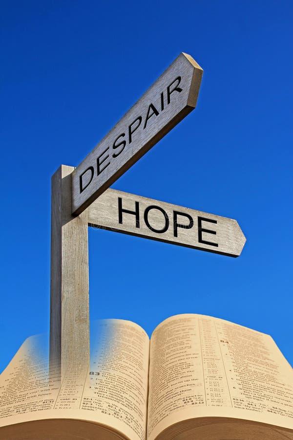 Bible spiritual direction arrow sign despair hope. Concept photo of despair versus hope showing direction arrow signs with open holy bible royalty free stock photography