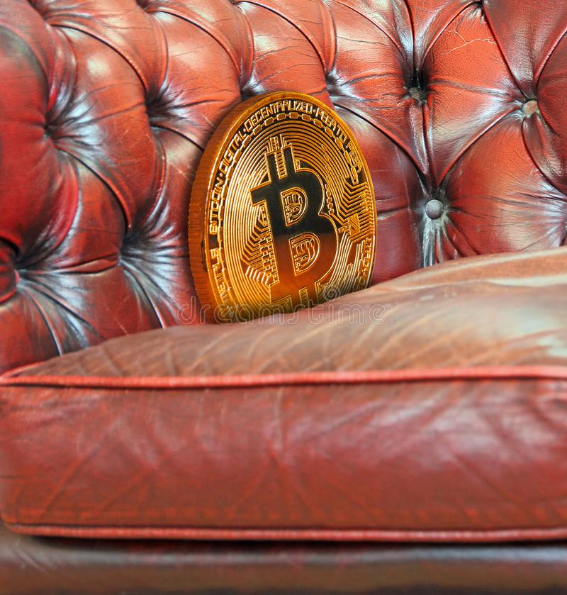 Gold bitcoin cryptocurrency lost down sofa armchair. Concept photo of digital cryptocurrency bitcoin lost down the side of a leather suite sofa armchair royalty free stock photo