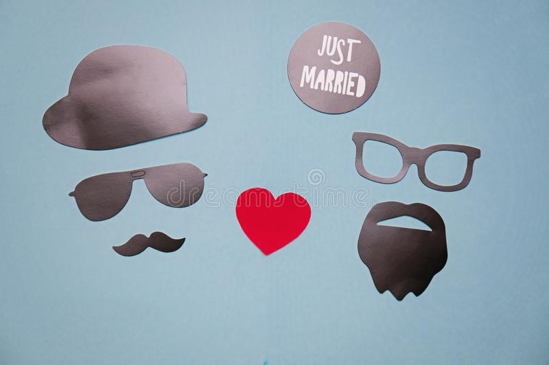 Concept photo of homosexuality and same-sex marriage: male masks with hearts on blue background. Concept photo of homosexuality: male masks with hearts on blue royalty free stock photos